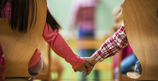 Kids in classroom holding hands