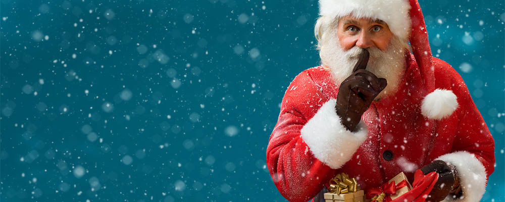 Santa Claus tiptoeing with bag of gifts