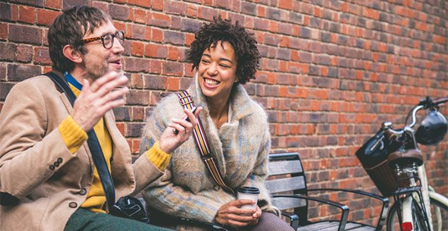 Couple talking seated on a bench outdoors