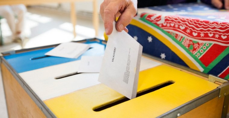 Voting in Sweden hand dropping ballot into voting box
