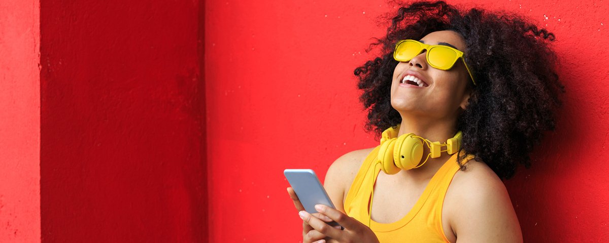 Smiling american-african woman listening music on smart phone