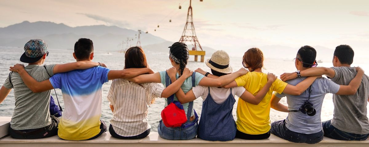 Group of Young friends sitting on a jetty