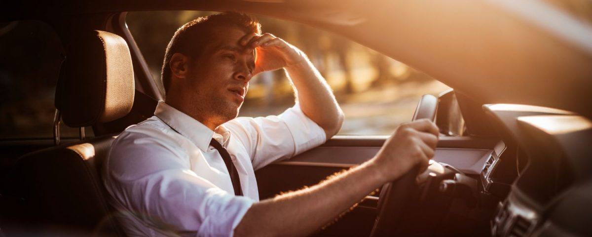 Man driving looking tired, burnt out