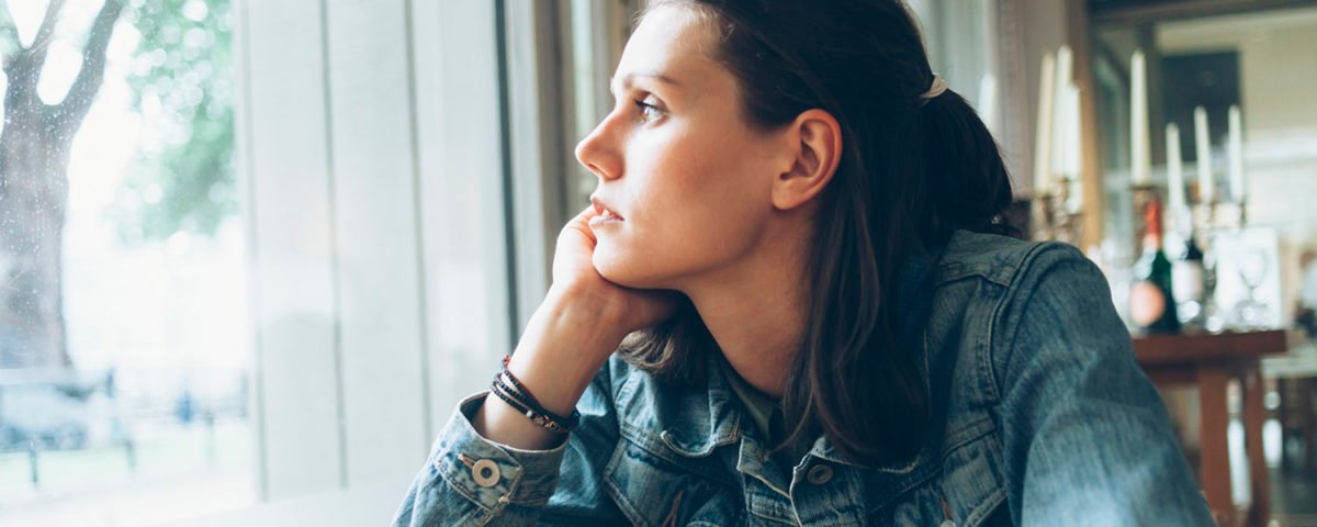 Pensive young woman sitting in cafe alone
