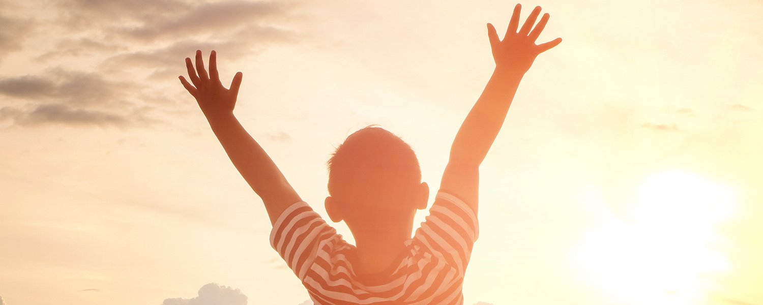 Boy with arms reaching up to the sky at sunrise