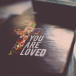 You are Loved text next to a flower-coloured cross cover on a Bible