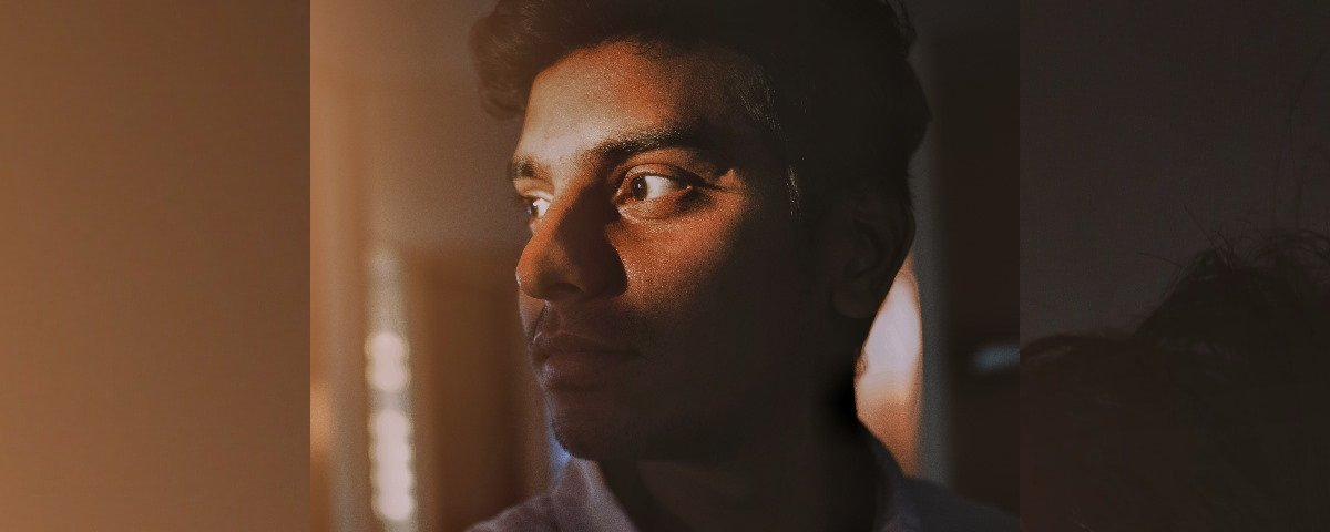 Young Indian Man looking out window -