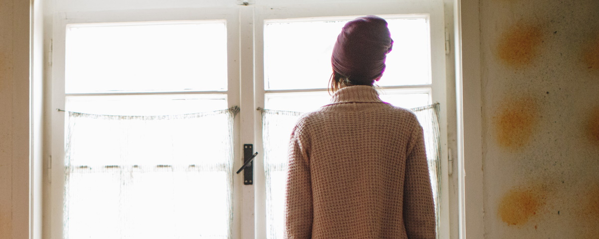Young woman looking out window 1200 x480