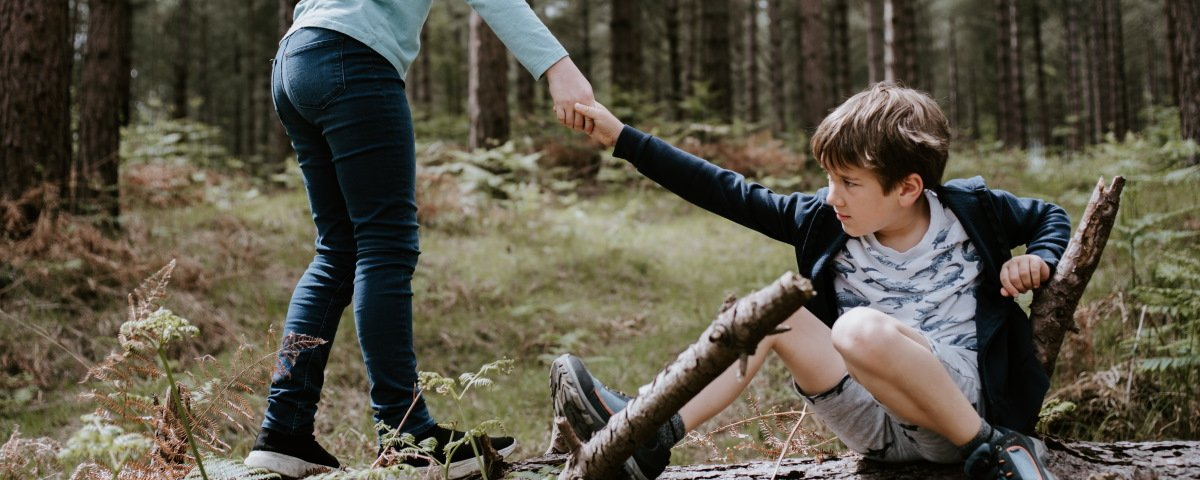 Girl helping boy over a log