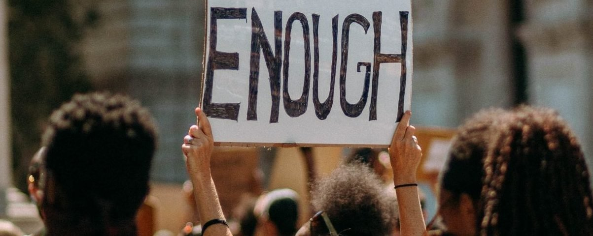 Protesting and sign with 'Enough' written on it