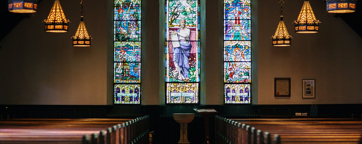 Inside a church with pews, stainglass windows and baptismal bath