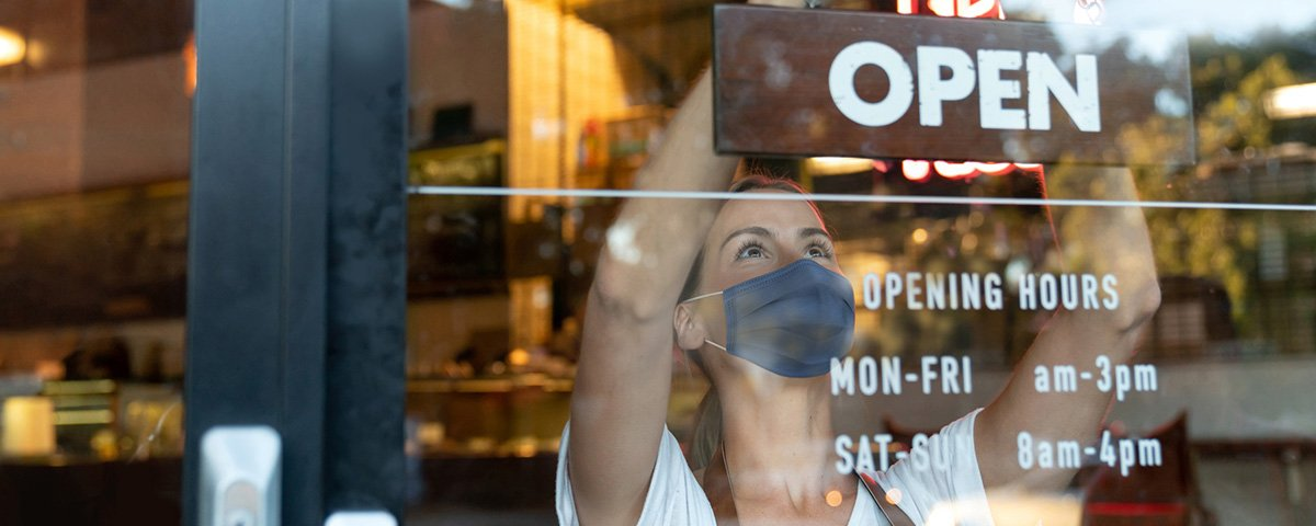 Open for Business sign with lady wearing a face mask