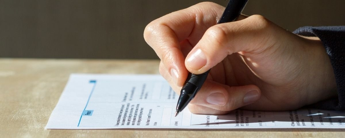 Hand writing with a pen filling out a Census form