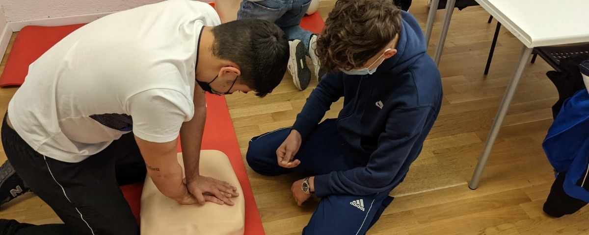 Two young adults, young men performing first aid CPR